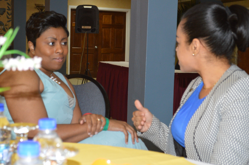 Carol Sankar sitting at a table speaking with another woman.