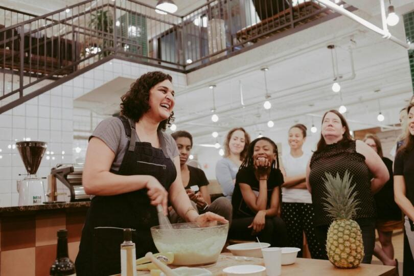 Pineapple's cofounder in the kitchen with a group of people, whipping something in a bowl