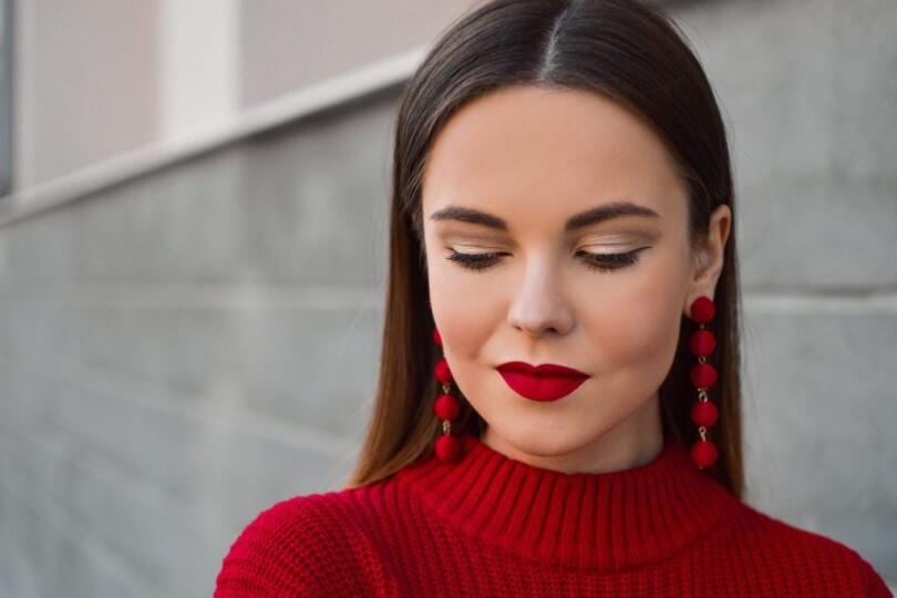 Woman wearing a red sweater and red lipstick