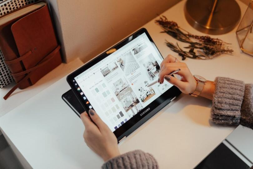 Woman's hand using a stylus to navigate a web page on a tablet
