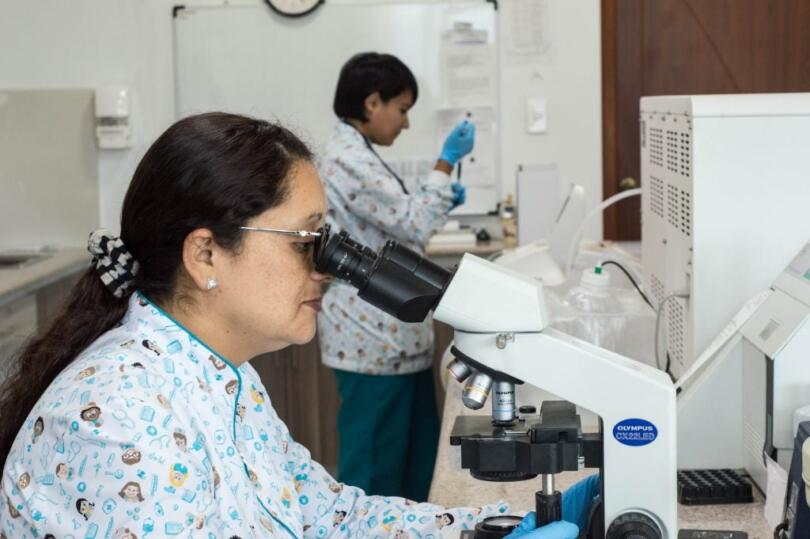 Woman in a lab looking into a microscope