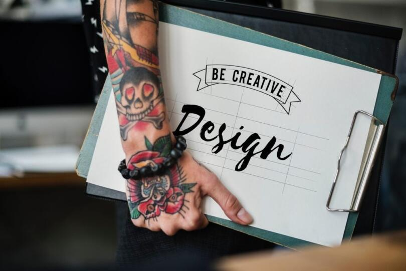 "Picture of an arm and hand with tattoos carrying a folder that says ""Be Creative Design"""