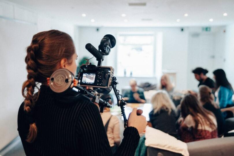Woman holding a camera video taping a meeting