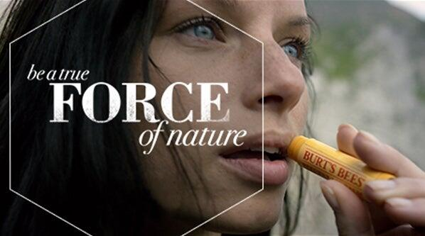 Photo from advertising video pictures a woman applying Burt's Bees to her lips