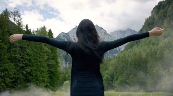 Woman standing with arms outstretched in a field with mountains in the background