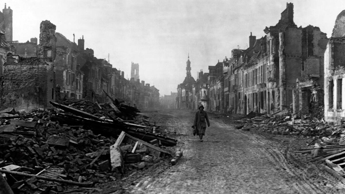 A german soldier walking through the ruins of Peronne.