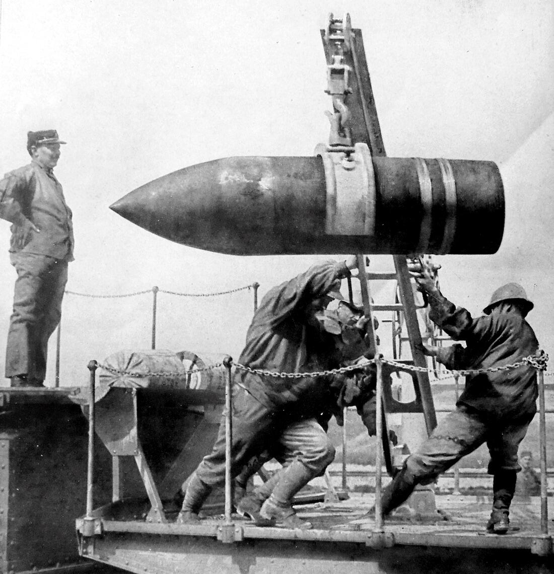 An artillery shell is hoisted into position by soldiers.