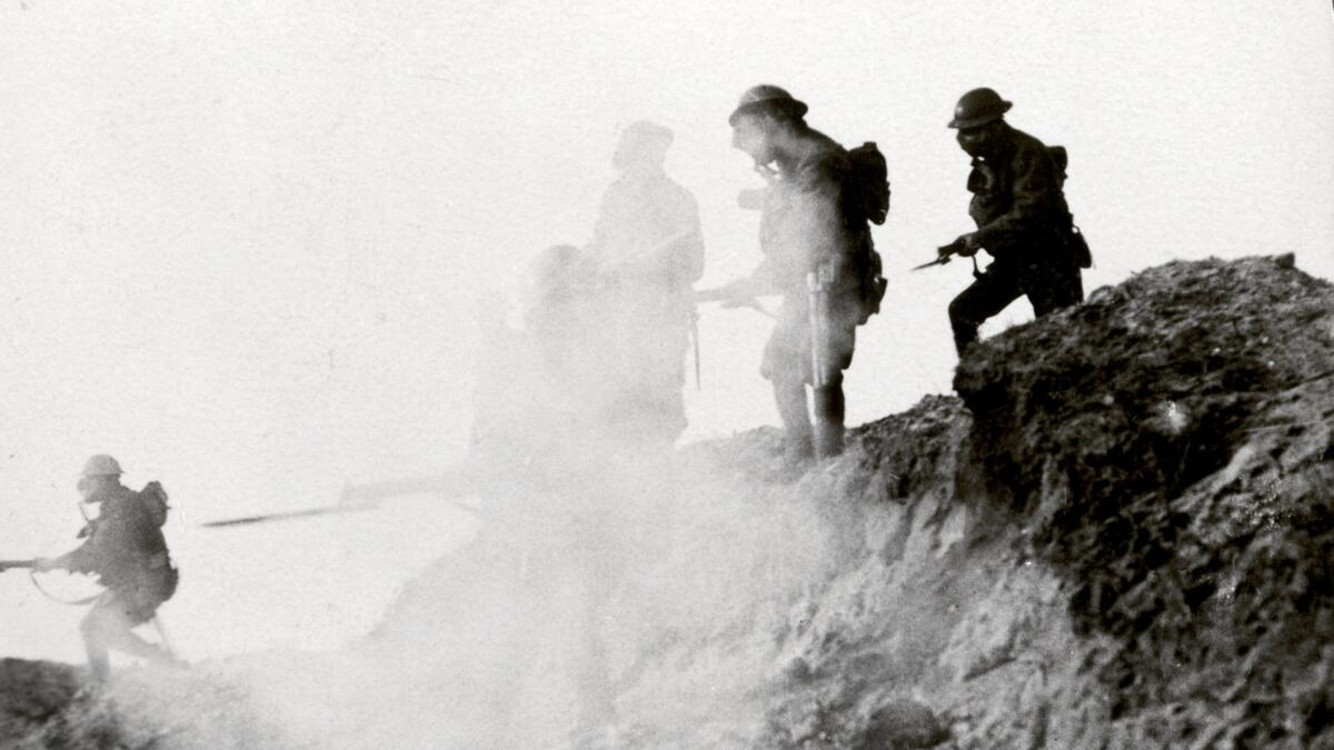 British soldiers advancing under cover of gas and smoke.