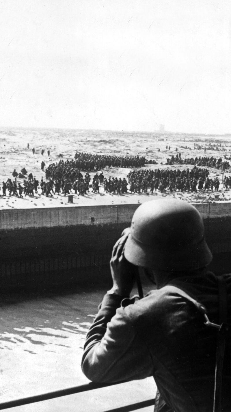 A German soldier looking out at Allied Forces trying to evacuate