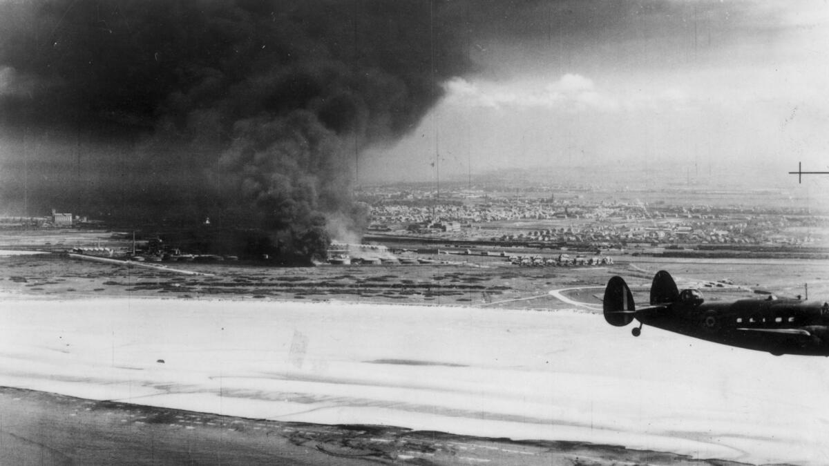 A Coastal Command Lockhead Hudson flying past burning oil tanks on Dunkirk beach