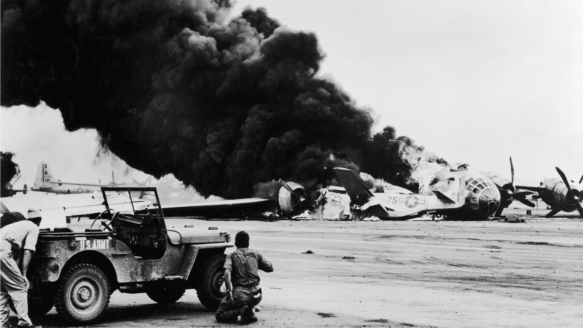 US servicemen shelter behind a jeep to avoid exploding ammunition as a B.29 Superfortress.