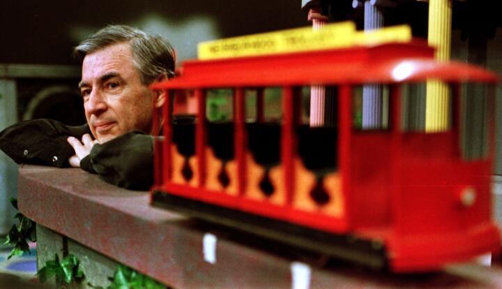 Television personality Fred Rogers leaning on a model railroad track at his Mr. Rogers studio