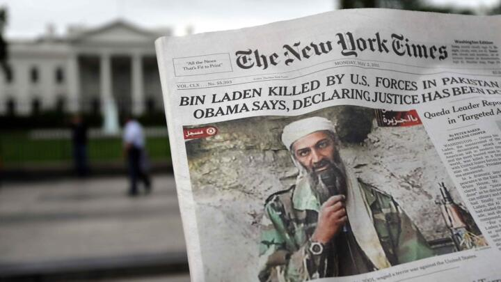 A man reads the front page of a newspaper featuring the news that Al-Qaeda leader Osama bin Laden was shot dead