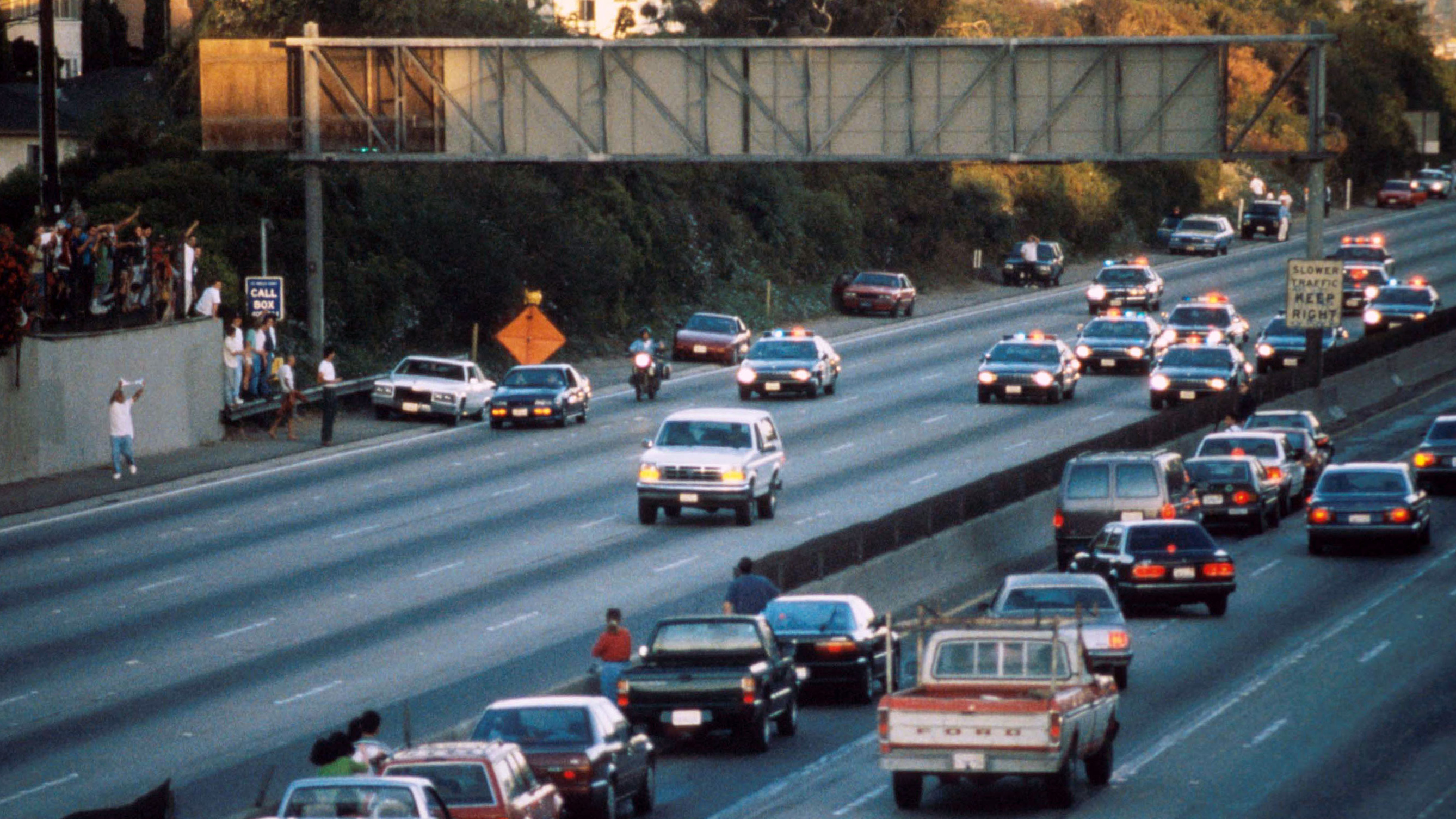 Motorists stop and wave as police cars pursue the Ford Bronco driven by Al Cowlings, carrying fugitive murder suspect O.J. Simpson, on a 90-minute slow-speed car chase June 17, 1994 on the 405 freeway in Los Angeles, California. (Credit: Jean-Marc Giboux/Liaison/Getty Images)
