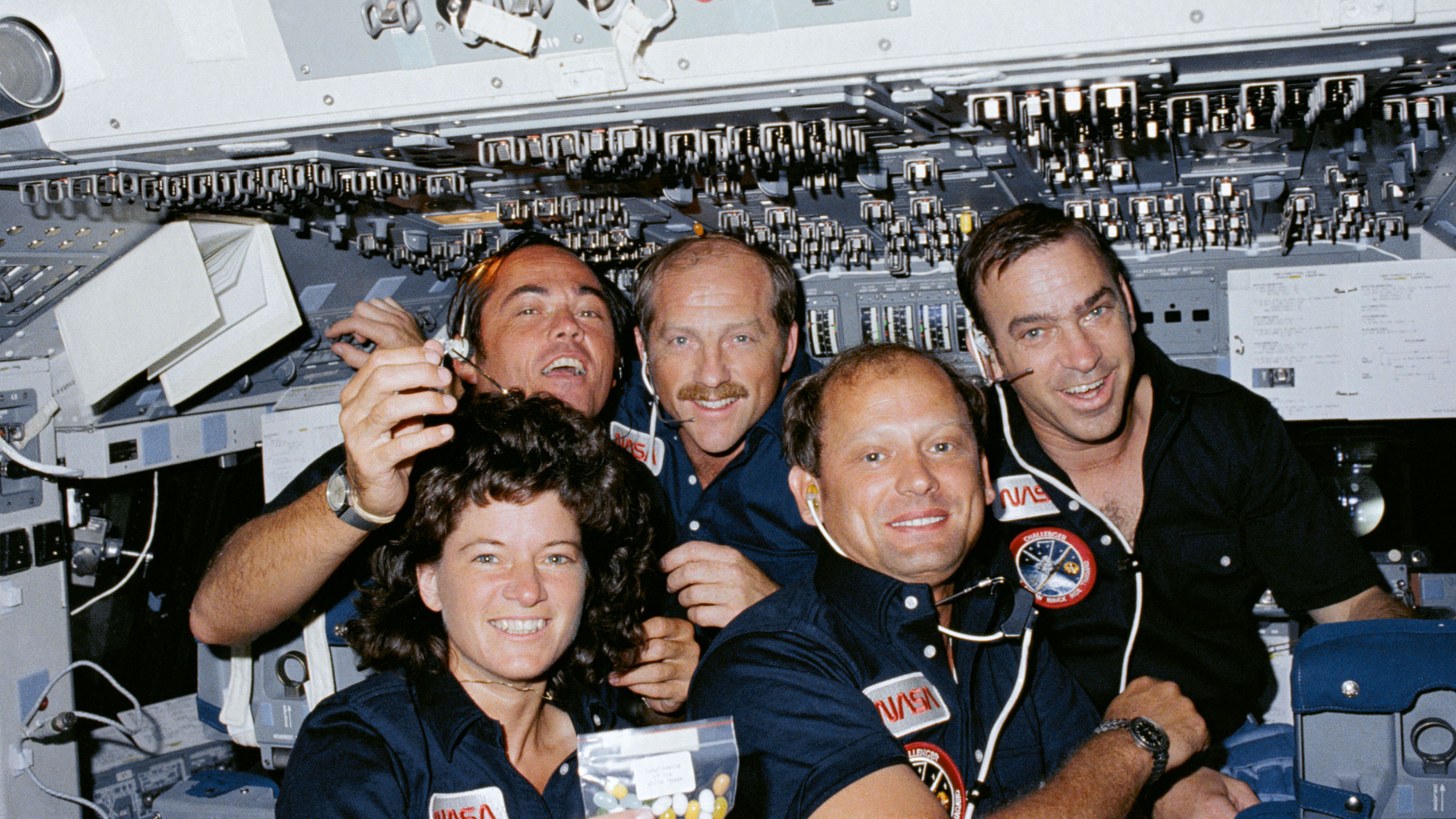 Space Shuttle Challenger's STS-7 crew poses for a group portrait on the forward flight deck. Left to right are Mission Specialist Sally Ride, Commander Robert Crippen, Pilot Frederick Hauck, Mission Specialist Norman Thagard and Mission Specialist John Fabian. (Credit: NASA)