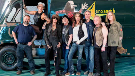 Four decades after the band used the van, the American Pickers and Aerosmith pose in front of the painstakingly restored van. (Credit: Zack Whitford for HISTORY