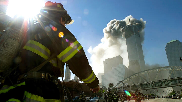 Firefighter looking up at a smoke-filled World Trade Center on September 11, 2001
