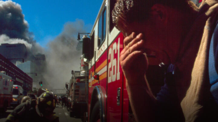A firefighter sitting by his truck looking exhausted as the smoke from the World Trade Center towers is behind him