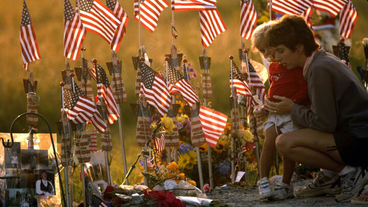 Mourners at the memorial for Flight 93 surrounded by American flags left by other mourners