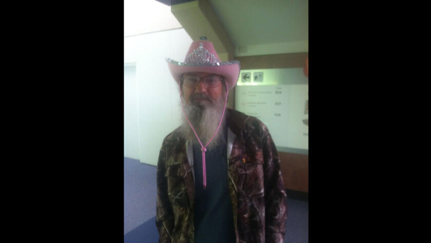Si models his most fashionable accessory, a pink cowgirl hat topped with a tiara, in a Dallas airport.