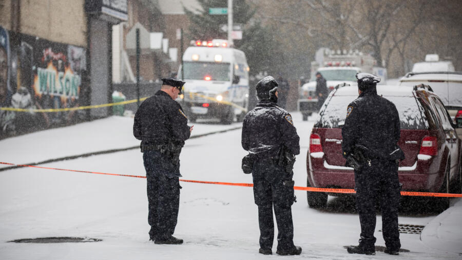 Police officers guard the perimeter of a crime scene in the winter. Photo by Andrew Burton/Getty Images.