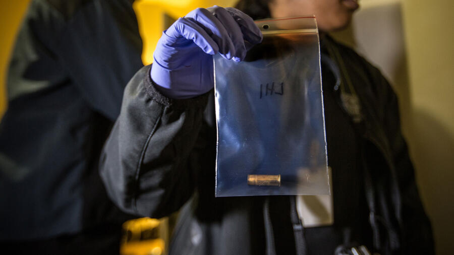 A (real-life) crime scene investigator holds an evidence bag containing a bullet casing.