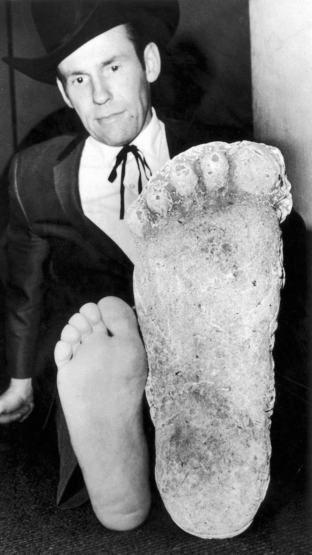 Roger Patterson comparing his foot with a plaster cast of a footprint by the purported 'Bigfoot' or 'Sasquatch'.