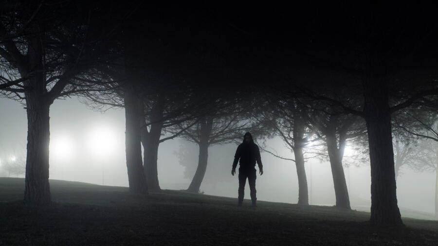 Silhouette of a creepy man standing in park at night