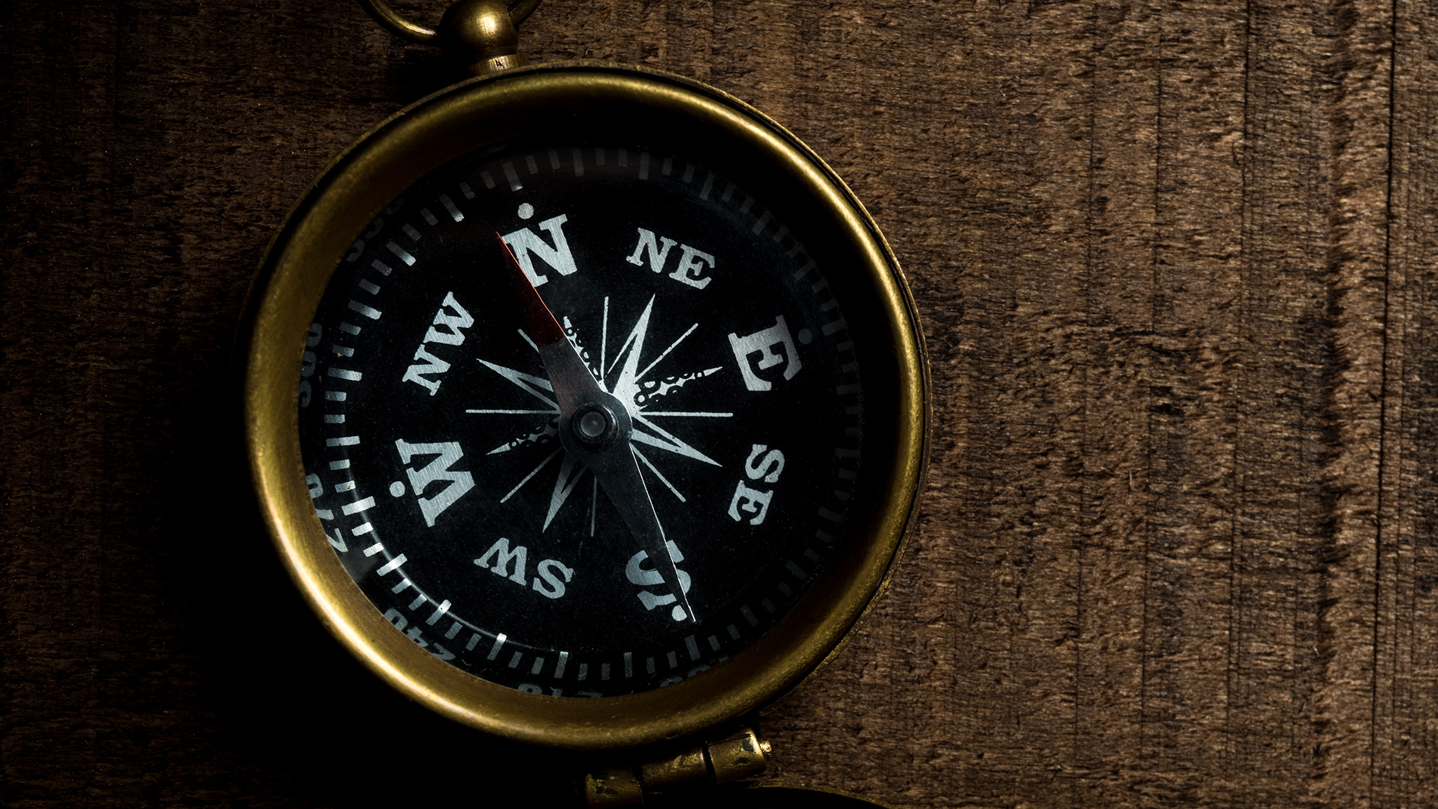 A compass sits on a wooden table