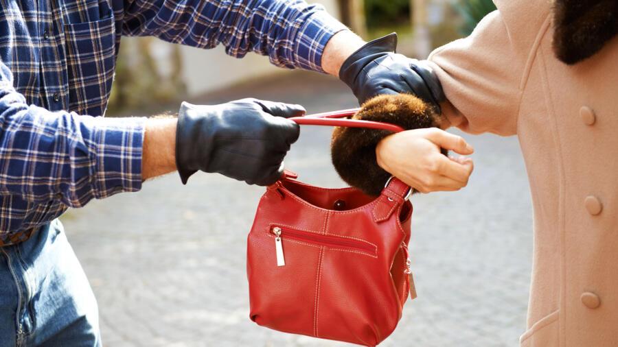 A mugger stealing a handbag