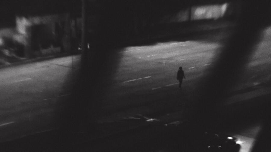 Woman walking in the road at night.