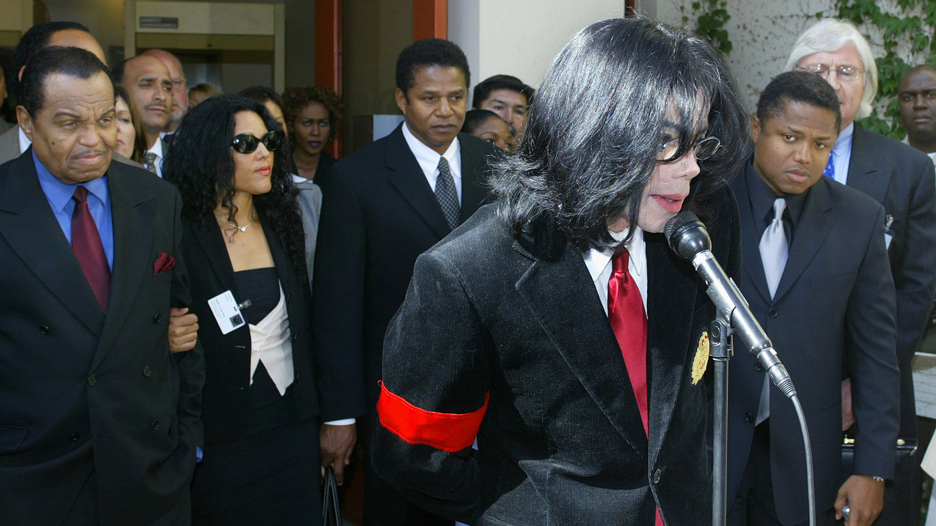Pop star Michael Jackson, center, speaks to the press following his indictment on charges related to child molestation